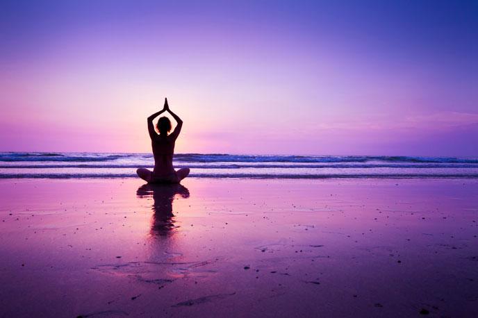 Woman practicing yoga on the beach. Source: https://www.flickr.com/photos/egizu/29438001551